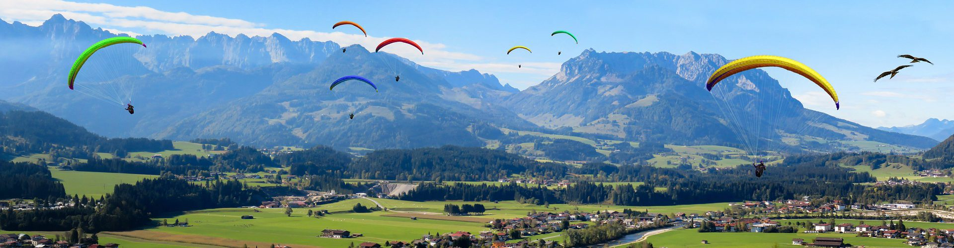 Paragliders in front of a mountain skyline