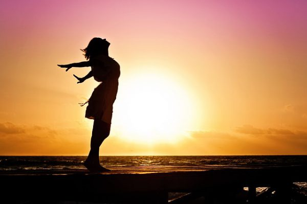 Women breaking free from her environment in front of sunset